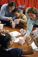 Elementary school students in a weekly Science Club at the Boys &amp; Girls Club in south Madison learn about symmetry and geology by growing sugar crystals, led by program coordinator Megan Chrysler (right) and undergraduate volunteer Adam Hofer (left). The statewide afterschool science education outreach program for economically disadvantaged youth is funded by the Ira and Ineva Reilly Baldwin Wisconsin Idea Endowment. Pictured are (clockwise from left) volunteer Natalia O'Laughlin, Darneisha (surname withheld), Megan Chrysler, and Johnetta Foster.<br /> <br /> Client: University of Wisconsin-Madison<br /> &copy; UW-Madison University Communications 608-262-0067<br /> Photo by: Michael Forster Rothbart<br /> Date:  2/05    File#:  D100 digital camera frame 1559.