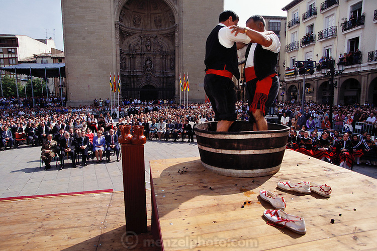 2 men in traditional costume stomp grapes barefoot on a stage in front of the cathedral at the yearly wine festival ceremony in Logroño, La Rioja Region, Spain.