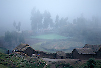 Mist passes over a small farm in the high Andes above Cuzco, Peru.