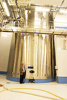 In the winery: One gigantic shining stainless steel vat used for blending the cuvee and a man standing next to it. The contents of the tank is 3241 hectolitres, the Union Champagne cooperative, also called Champagne de Saint Gall in Avize, Cote des Blancs, Champagne, Marne, Ardennes, France