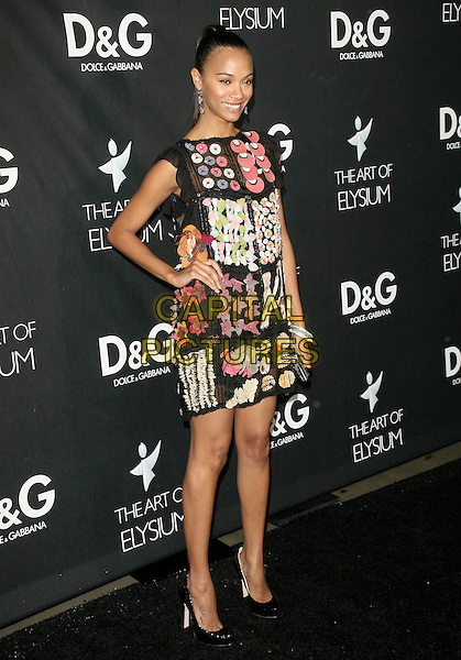 ZOE SALDANA.the D&G celebration of the opening of the flagship boutique on Robertson Boulevardin in Beverly Hills, California, USA..December 15th, 2008.full length black dress red pink sleeveless clutch bag pattern print floral print hand on hip .CAP/DVS.©Debbie VanStory/Capital Pictures.