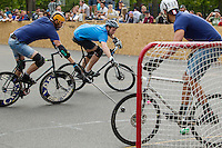17 AUG 2014 - LONDON, GBR - A player from Sentinels (in light blue) tries to find an angle to shoot from during the game against Jackie Chan is Dead (dark blue) at the 2014 London Open Bike Polo tournament in Highbury Fields in London, Great Britain (PHOTO COPYRIGHT © 2014 NIGEL FARROW, ALL RIGHTS RESERVED)