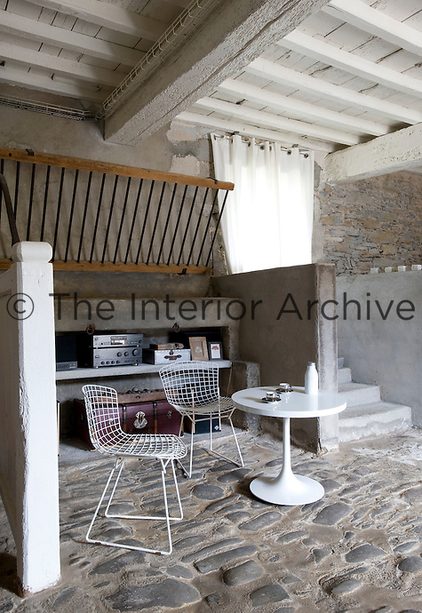 A pair of Bertoia chairs beside a Saarinen table in this stone-floored former barn turned living space which features the original hay rack on the rear wall