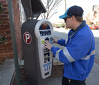 NWA Democrat-Gazette/ANDY SHUPE<br /> Luke Bouxsein, a parking enforcement officer with the city of Fayetteville, repairs Friday, March 2, 2018, a parking pay station off West Avenue in Fayetteville. Consulting firm Nelson/Nygaard has completed a nearly 2-year-long study of parking downtown. On Tuesday, the City Council will discuss implementing the first phase of the study&rsquo;s recommendations. One of the first steps of the recommended downtown parking plan is rebranding parking enforcement officers as customer servers, rather than ticket-writers.