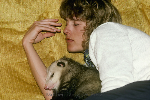 Woman and young opossum, Didelphis marsupialis, sleeping on couch