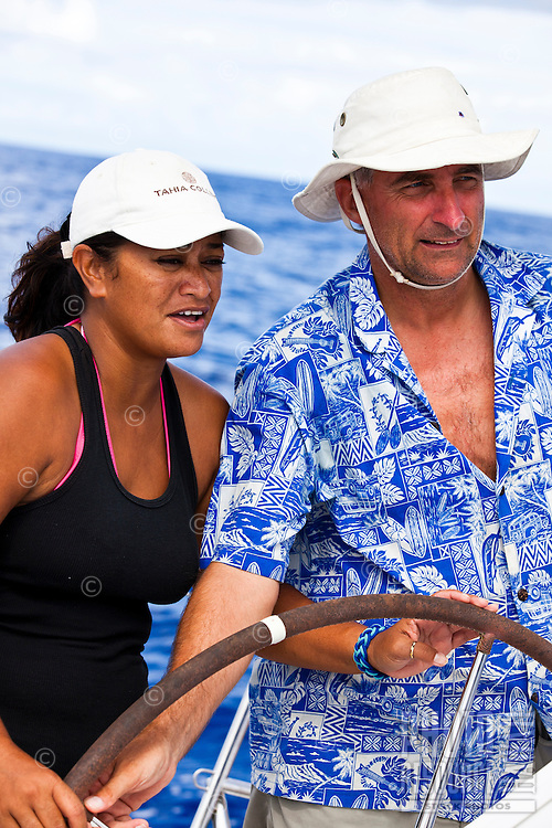 Caucasian man teaches Tahitian woman steering while racing in the first leg of the Tahiti Pearl Regatta, from Raiatea to Bora Bora