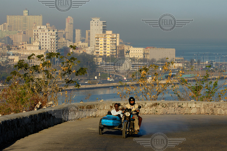 A motorbike with a sidecar travels up Casablanca Hill, which overlooks Havana's harbour..