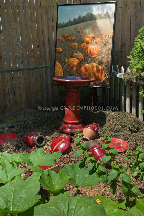 Decorating the pumpkin patch garden with old pottery and artist painting of pumpkins ripe