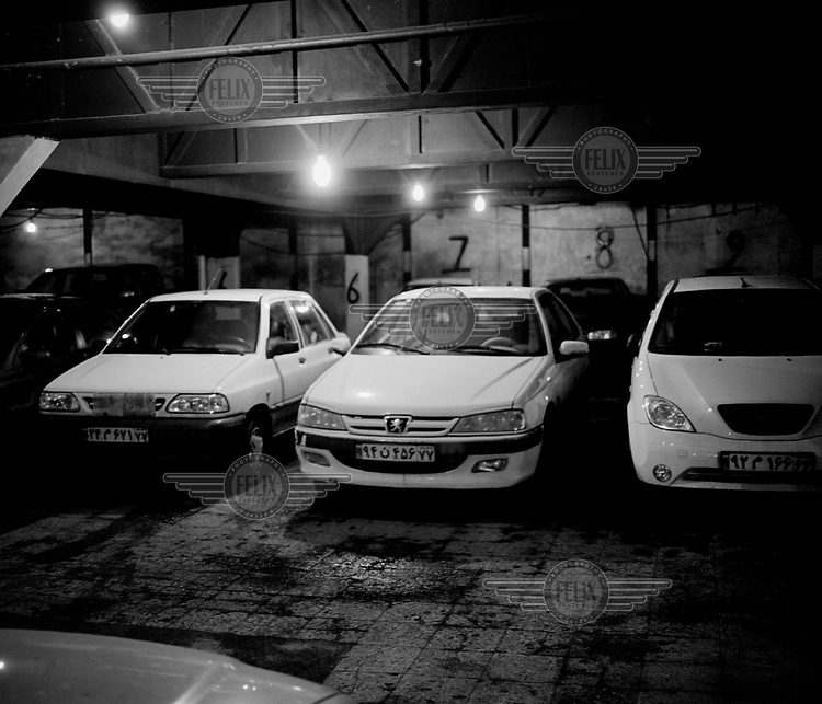 A locally built Peugeot and other cars parked in an underground car park.