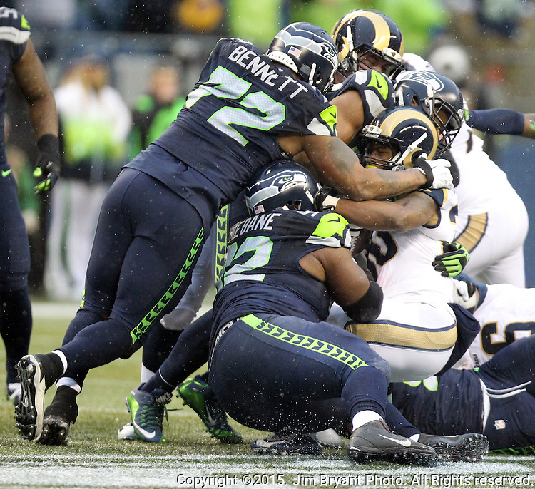 Seattle Seahawks defenses, Cassius Marsh (91), Brandon Mebane (92),  Bobby Wagner (54) and Michael Bennett (72) team up to tackle St. Louis Rams running back Benny Cunningham (36) at CenturyLink Field in Seattle, Washington on December 27, 2015.  The Rams beat the Seahawks 23-17.      ©2015. Jim Bryant Photo. All Rights Reserved