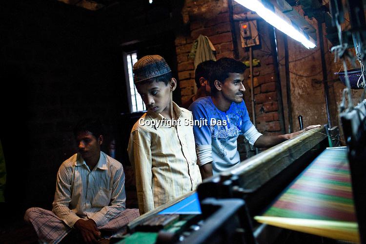Weavers use machine looms to weave the famous Benaresi silk saris in his workspace in Gazi Sadullahpura Bade Bazaar in Varanasi in Uttar Pradesh, India. Photograph: Sanjit Das/Panos