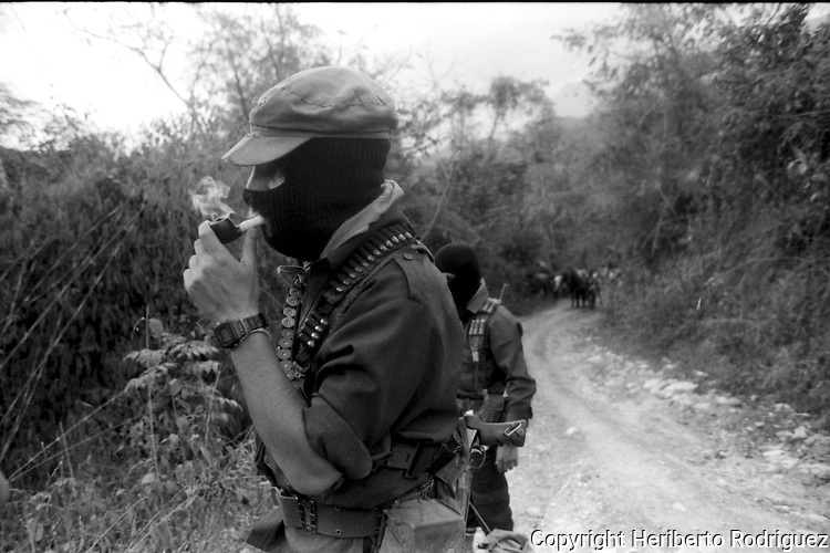 Subcomandante Marcos smokes his pipe as he inspects a road around  the Zapatista stronghold of Prado Pacayal, in southern state of Chiapas, March 22, 1994.  Photo by Heriberto Rodriguez