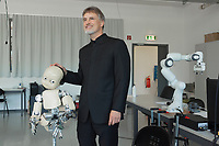 """Switzerland. Canton Ticino. Manno. IDSIA. Robot lab. Jürgen Schmidhuber (born 17 January 1963) is a computer scientist most noted for his work in the field of artificial intelligence, deep learning and artificial neural networks. He is a co-director of the Dalle Molle Institute for Artificial Intelligence Research in Manno. The native german Bavarian is sometimes called the """"father of (modern) AI"""" or, the """"father of deep learning"""". He stands close to the robot iCub. iCub is a 1 metre tall open source robotics humanoid robot testbed for research into human cognition and artificial intelligence. The Dalle Molle Institute for Artificial Intelligence Research (Italian: Istituto Dalle Molle di Studi sull'Intelligenza Artificiale, IDSIA) is a research institution in Manno. It was founded in 1988 by Angelo Dalle Molle through the private Fondation Dalle Molle. In 2000 it became a public research institute, affiliated with the University of Lugano and SUPSI in Ticino, Switzerland. In 1997 it was listed among the top ten artificial intelligence laboratories, and among the top four in the field of biologically-inspired AI. In 2007 a robotics lab with focus on intelligent and learning robots, especially in the fields of swarm and humanoid robotics, was established. Manno is a municipality in the district of Lugano. 8.05.2020 © 2020 Didier Ruef"""