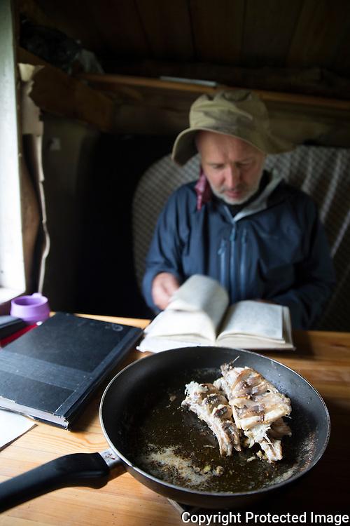 Mann leser hyttebok i gamme. Panne med stekt harr på bordet. ---- Man reading guest book in cabin.
