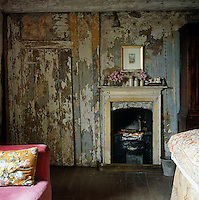 Generations of wallpaper and paint have peeled away to reveal the original wood and plaster on the walls of this bedroom
