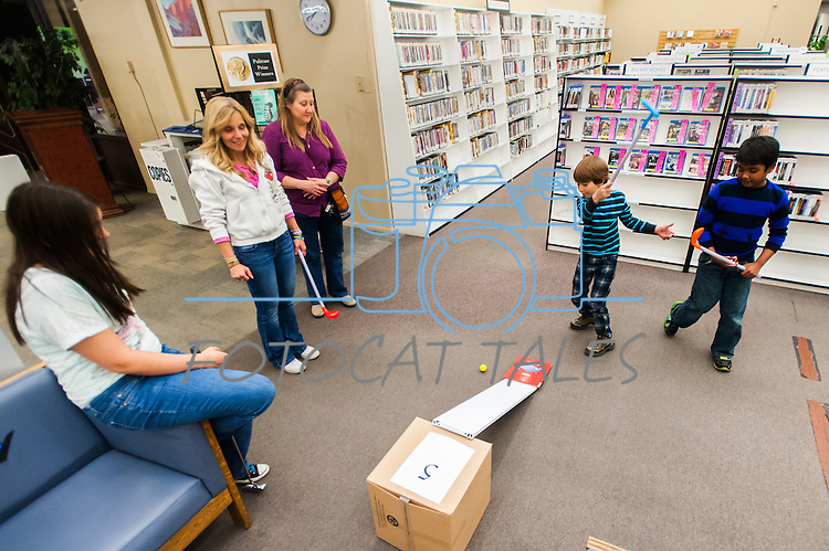 Alex Wells misses a ramp shot on hole 5 during the Mini Golf Night at the Carson City Library on Friday, May 9, 2014. Kids and parents built a custom mini golf course throughout the library using anything at their disposal and engineering ideas to make a difficult course. Everything from tables to shelves were used to create creative courses.<br />