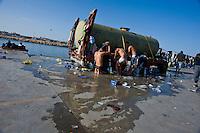 Immigrati Tunisini si lavano utilizzando l'acqua di un vecchio cassone messo loro a disposizione nel porto di Lampedusa
