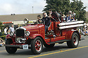Vintage fire truck in parade at Silverdale, WA Kitsap County Whaling Days community event. Stock photography by Olympic Photo Group