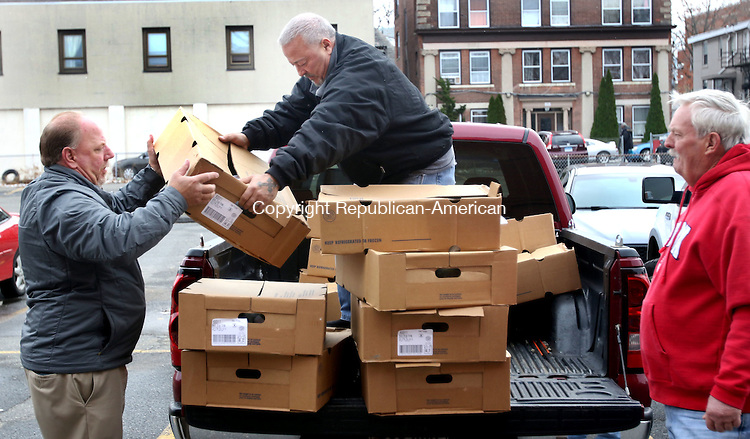 WATERBURY CT. 21 November 2016-112116SV02-From left, Wolcott Mayor Tom Dunn, and Tony Cavallo, co-chairman of the Bill Wildman Memorial turkey drive, get some help from John Roberge while handing out some of the 200 turkeys that were donated by the Elks Club in Waterbury Monday.<br /> Steven Valenti Republican-American