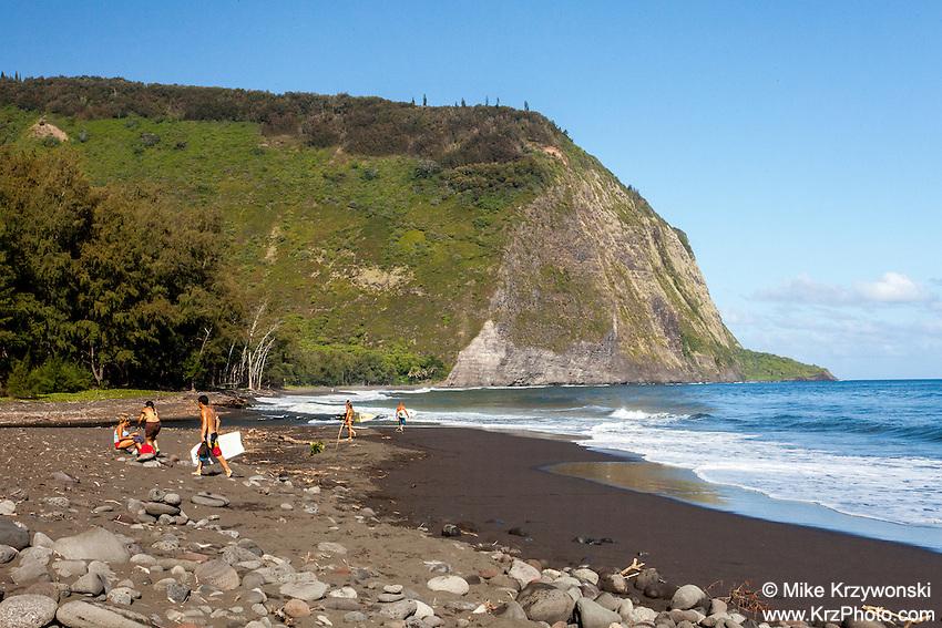 Kids w/ surfboards walking on beach in Waipio Valley, Big Island, Hawaii