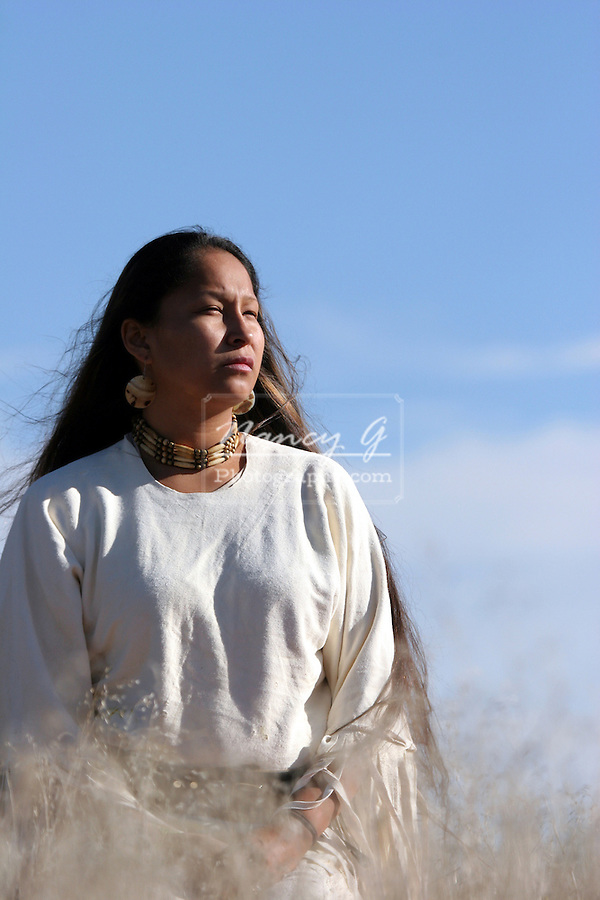 A young Native American Indian Woman looking into the sun in the grasses of South Dakota
