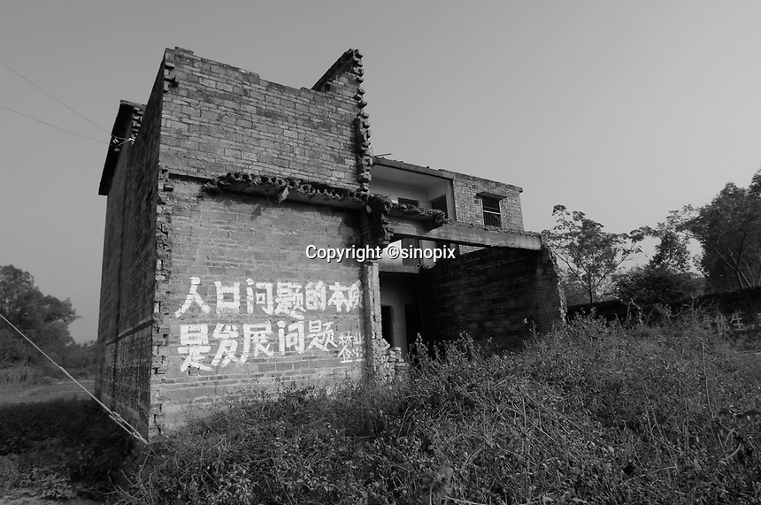 "A house in Bobai county outside Yingqiao that has been smashed up. The house and the surrounding area have slogans from the One Child Policy, ""fewer babies better life"" and "" a sensible birth policy is essential for development""."