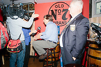 A NECN reporter interviews a man as Republican presidential candidate and New Jersey governor Chris Christie greets supporters at Tandy's Top Shelf Pub in Concord, New Hampshire.
