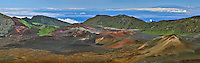 Expansive panoramic view of  multi colored cinder cones and lava flows in the crater in HALEAKALA NATIONAL PARK on Maui in Hawaii USA.  Some clouds and blue sky enhance the beauty of this rugged landscape