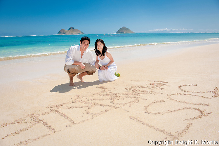 "Asian bride and groom pose with with their ""Just Married"" sign in the sand during a stroll on Lanikai beach."