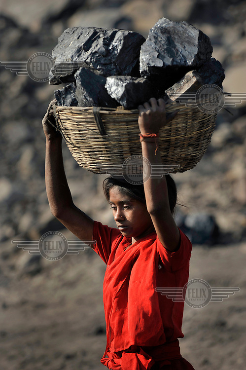 A girl carries a huge basket of lump coal on her head. The coal is illegally collected from rubble at the edge of a massive open cast mine. Many villagers survive by selling coal that has been illegally collected.