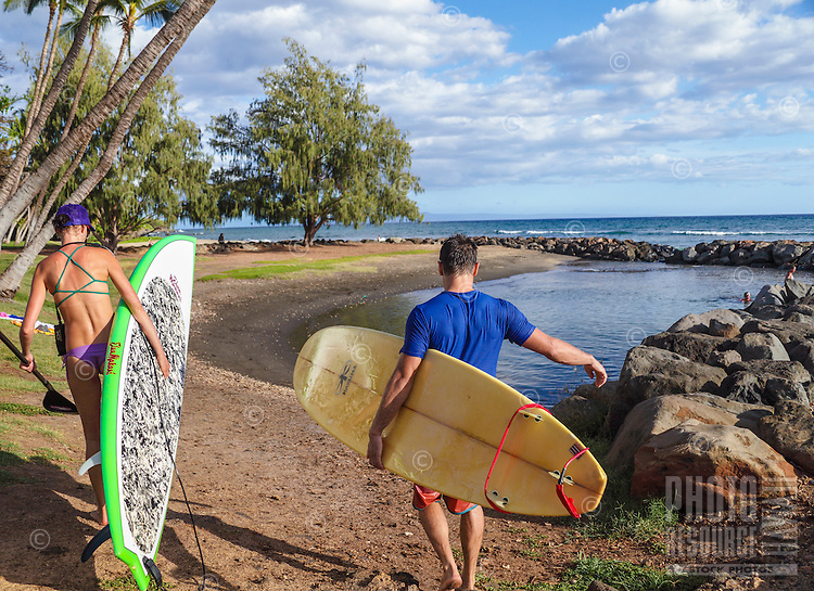 A surfer and a standup paddler make their way to the beach at Launiupoko State Wayside Park, Maui. (NOTE: only the couple in the foreground are model released; the others are not.)