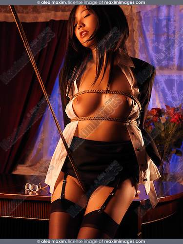 Beautiful sexy young asian woman standing at a table tied up with Japanese rope bondage Shibari