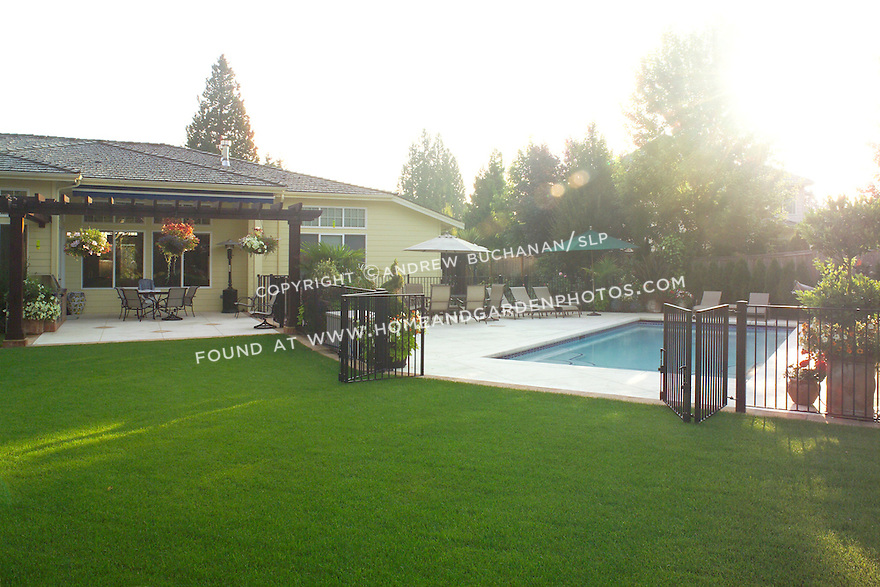 A wide shot of a suburban back yard at sunrise, showcasing a beautifully manicured, lush green lawn, a decorative patio bordered by an overhead arbor that hangs with baskets of colorful summer annuals, and a built-in, below ground swimming pool surrounded by comfortable lounge chairs.