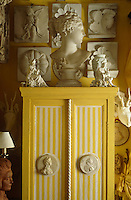 Casts of architectural details cover the walls of the living room and a Greek bust and figurines sit on top of a yellow and white striped cabinet