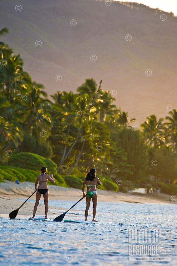 Young women standup paddle (SUP) at sunset off the shores of Mokuleia