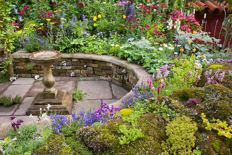 Colorful mixed perennial flower garden with Delphinium, sempervivum rock garden, bird bath, and climbing plants, circular sunken patio, raised beds, blue,yellow, red, pink colors
