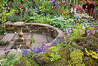 Colorful mixed perennial flower garden with Delphinium, sempervivum rock garden, bird bath, and climbing plants, circular sunken patio, raised beds, blue,yellow, red, pink colors