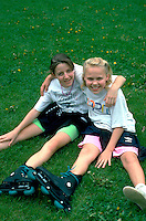 Two 10 year old friends resting on ground after rollerblading.  Minneapolis  Minnesota USA