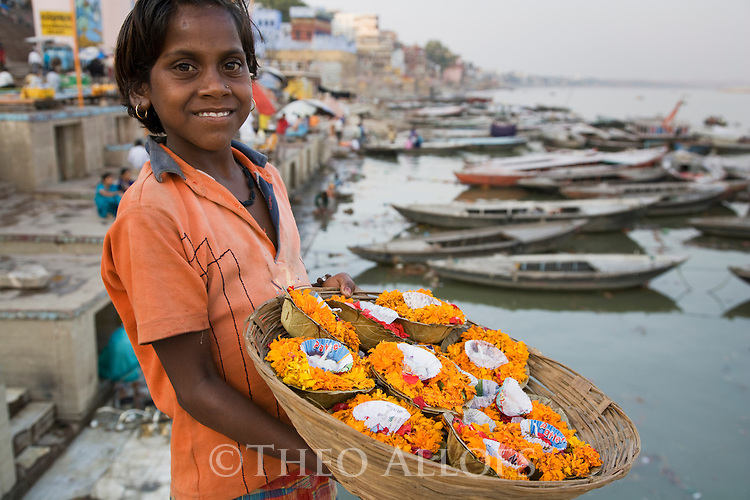 Young girl selling flower candles on the Ghats (stairs) of the Ganges River;  Varanasi has been a cultural and religious center in northern India for several thousand years, Varanasi, Uttar Pradesh, India --- Model Released
