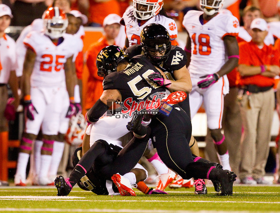 Andre Ellington (23) of the Clemson Tigers is tackled by Kevin Johnson (9) and Nikita Whitlock (50) of the Wake Forest Demon Deacons at BB&T Field on October 25, 2012 in Winston-Salem, North Carolina.  The Tigers defeated the Demon Deacons 42-13.  (Brian Westerholt/Sports On Film)