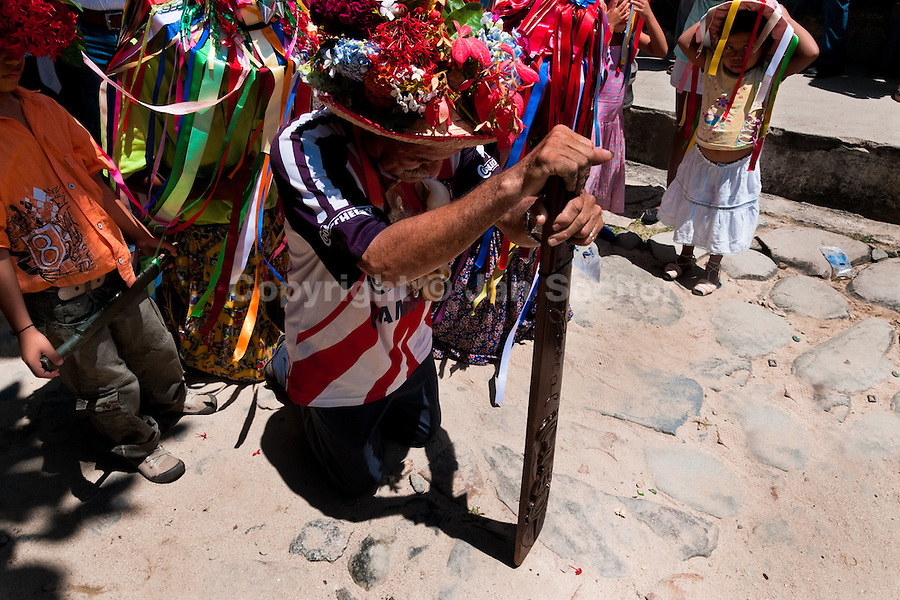 """A Negros dancer kneels with his wooden machete in the religious procession in Atanquez (Sierra Nevada), Colombia, 3 June 2010. A colorful celebration of Corpus Christi is held in the Kankuamo Indians territory every year. """"The Dance of the Devils"""" is an ancient tradition kept for centuries on the Colombia's Caribbean coast. This Christian religious event usually coincides with the summer solstice, which has always been the key point for the native cultures and for the black African slaves. Due to this confluence, the Kankuamo myths, the African animistic rites and other Pre-Columbian features have blended with the Spanish Catholic festival into a lively spectacle."""