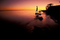 Australia, Queensland, Great Barrier Reef, Heron Island, woman on shoreline at sunset.  MR availabl