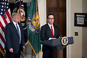 US President Donald J. Trump (L) listens as Secretary of Treasury Steven Mnuchin (R) delivers remarks in the US Treasury Department building in Washington, DC, USA, 21 April 2017. President Trump is making his first visit to the Treasury Department for a memorandum signing ceremony with Secretary Mnuchin.<br /> Credit: Shawn Thew / Pool via CNP