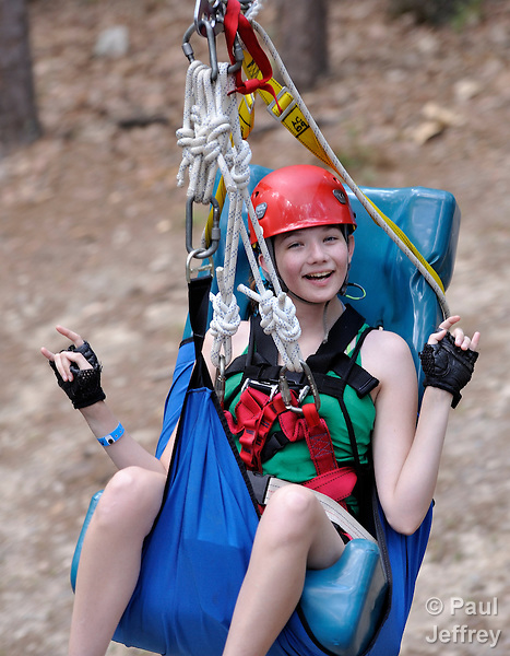 Camper Maddie Kannady rides a zip line through the forest at Camp Aldersgate in Little Rock, Arkansas. The camp, supported by United Methodist Women, offers children suffering from a variety of disabilities a safe and fun experience similar to that which normally-abled children often enjoy.