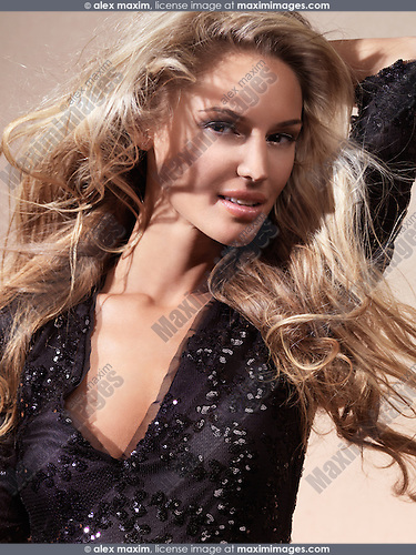 Portrait of a beautiful smiling young woman with long flying blond hair
