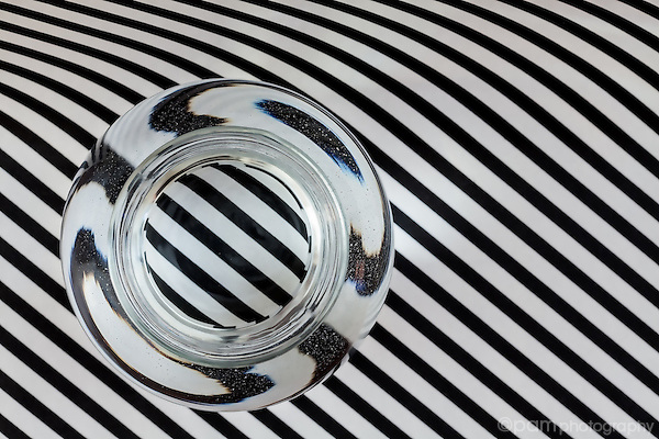 Black and white abstract of lines and circles created by water refraction through glass vase