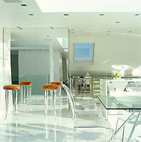 Four Philippe Starck stools with orange seats stand in the kitchen area of the open-plan penthouse