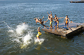 Santarem, Brazil. Boys playing in the river, diving from a wooden pontoon.