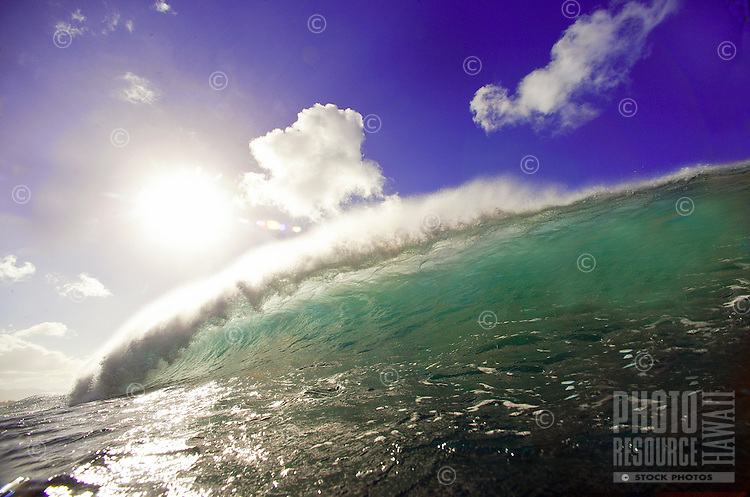 clean blue/green water reflects the sun as wave breaks under blue sky