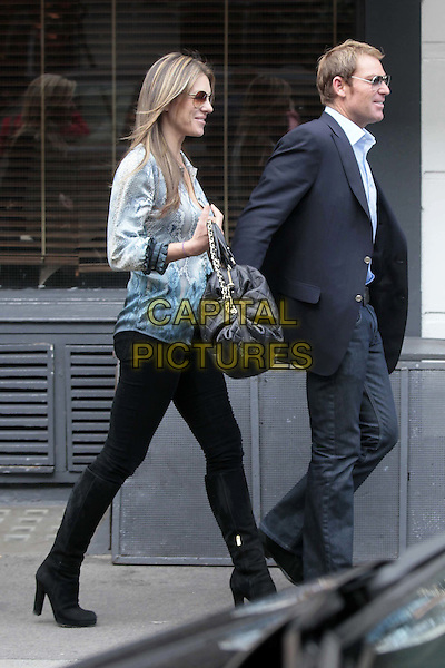 Elizabeth Hurley & Shane Warne .Leaving the San Lorenzo restaurant  in Chelsea, London, England..October 13th, 2011.liz full length couple side profile black bag purse jeans denim boots tucked in blue turquoise white blouse top suit jacket jeans denim sunglasses shades.CAP/HIL.©John Hillcoat/Capital Pictures.